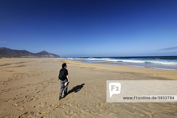 Frau mit Rucksack läuft an Playa de Cofete  Jandia   Fuerteventura   Kanarische Inseln