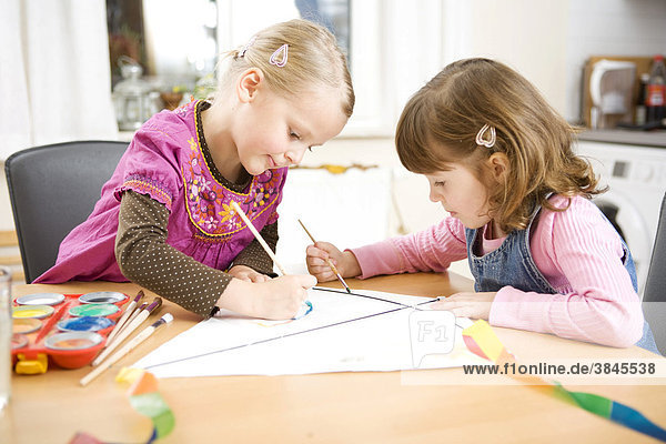 Two girls painting with water colours