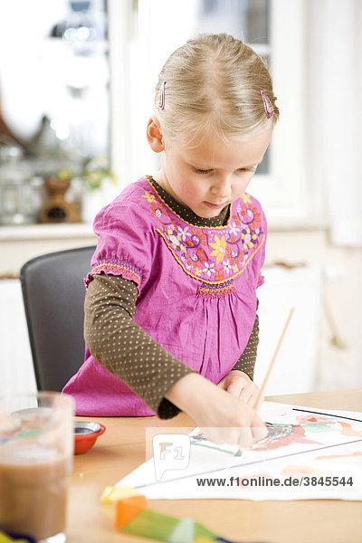 Ein Mädchen malt mit Wasserfarben