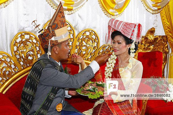 Bride and groom  traditional mutual feeding  wedding ceremony  Siantar  Batak region  Sumatra  Indonesia  Asia