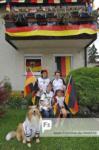Fans der deutschen Nationalmannschaft in Nationaltrikots mit Deutschlandflaggen vor geschmücktem Wohnhaus  Stuttgart  Baden-Württemberg  Deutschland  Europa