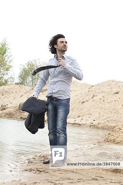Junger Mann am Seestrand entkleidet sich