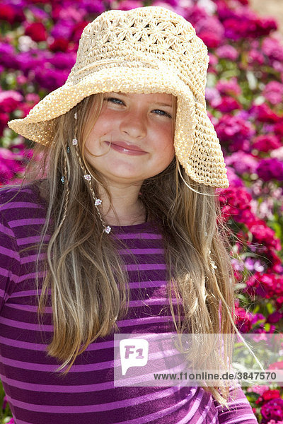 Girl with straw hat  8 years old  standing on a box with Sweet William carnations
