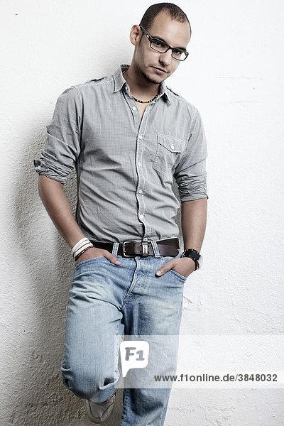 Junger Mann mit Brille Jeans und Hemd steht angelehnt vor einer Wand  die Hände in den Hosentaschen