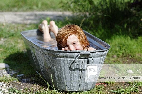 rothaariger junge beim erfrischen baden planschen in einer zinkwanne ibldwb01584233. Black Bedroom Furniture Sets. Home Design Ideas