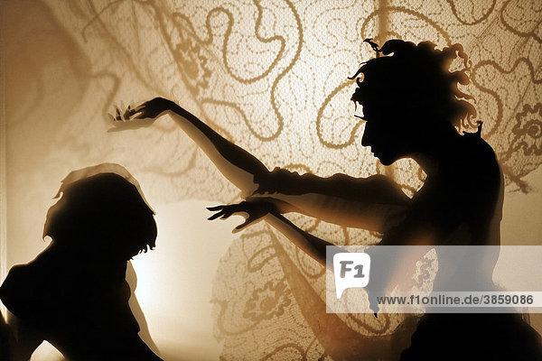 Frau verhext Mann  Projektion von Scherenschnittfiguren auf einer beleuchteten Gardine  Schattentheater  Rundgang Kunstakademie Düsseldorf  Nordrhein-Westfalen  Deutschland  Europa
