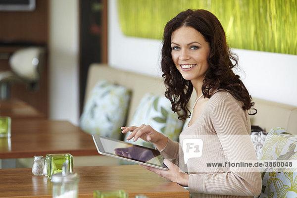 Junge Frau mit eBook Lesegerät iPad an Cafetisch