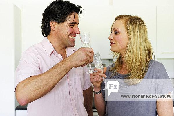 Junges Paar prostet sich mit Champagner zu