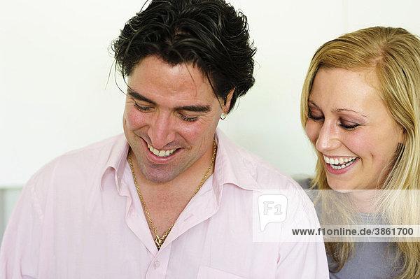 Junge Frau schaut ihrem Mann über die Schulter