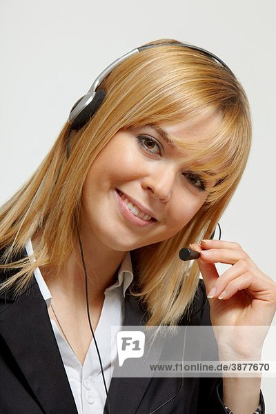 Happy blonde business woman with headset working in a call centre