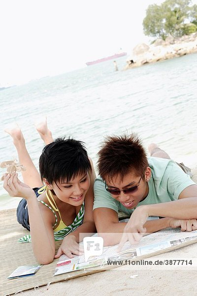 Young asian couple looking at map