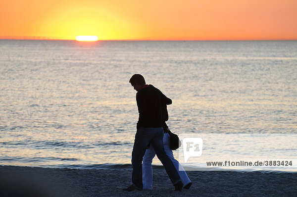 Spaziergänger  Paar am Strand bei Sonnenuntergang über der Ostsee  Ostseebad Warnemünde bei Rostock  Mecklenburg-Vorpommern  Deutschland  Europa