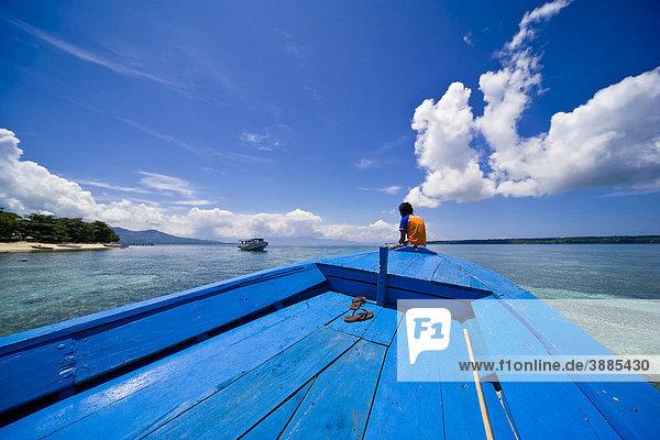 Junge Frau sitzt am Bug eines Holzboots  Siladen Insel  Sulawesi  Indonesien  Südostasien