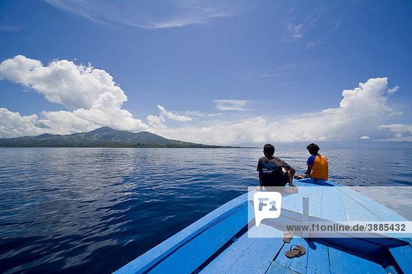 Junges Paar sitzt am Bug eines Holzboots  Siladen Insel  Sulawesi  Indonesien  Südostasien