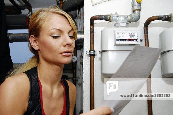 Junge Frau mit Heizkostenabrechnung am Gaszähler