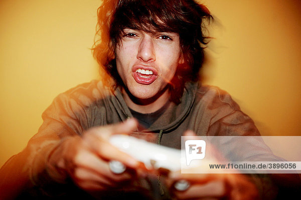 Junger Mann hält Spielkonsole in der Hand und regt sich über das Computerspiel auf
