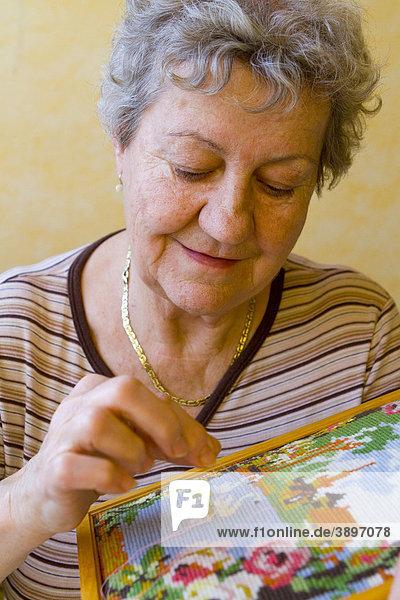 Pensionistin beim Sticken