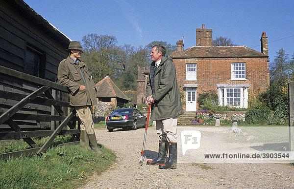 Farmer und Agrarwissenschaftler sprechen in der Zufahrt vor einem Bauernhaus miteinander  Hertfordshire  England  Vereinigtes Königreich  Europa