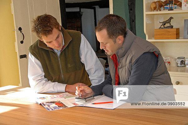 Bauer und Agrarwissenschaftler diskutieren ihre Strategie in der Küche eines Bauernhofs  Mentmore  Buckinghamshire  England  Vereinigtes Königreich  Europa