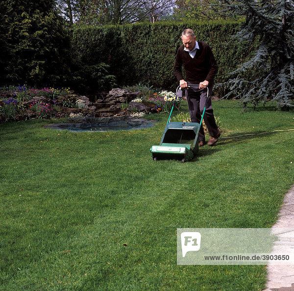 Mann mäht den Rasen mit Elektro-Rasenmäher im Garten