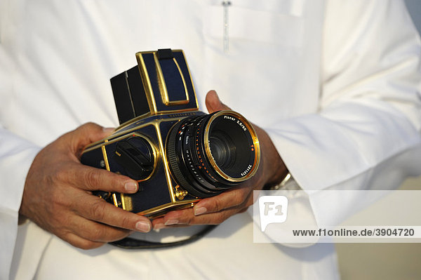Arabians presenting his gilded Hasselblad with Carl Zeiss Planar Lens 2  8-80mm