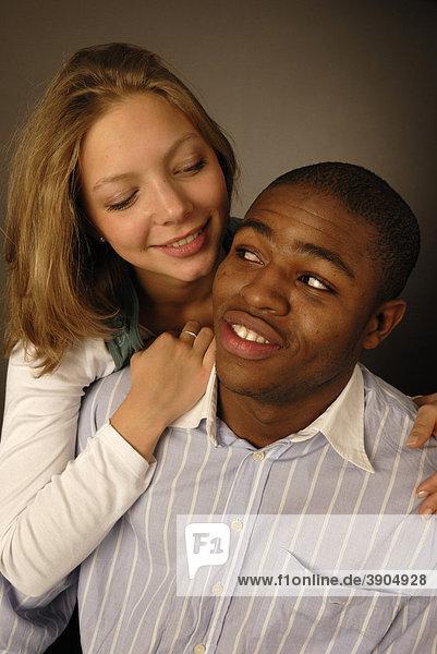 Junges verliebtes Paar  schwarze und weiße Hautfarbe  Afrikaner und Europäerin  Teenager  lächelnd