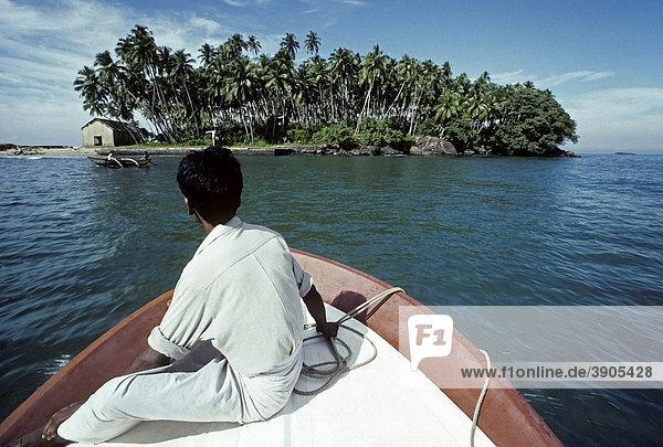 Junger singhalesischer Mann fährt auf einem Boot zu einer kleinen Palmeninsel  Sri Lanka  Ceylon  Südasien  Asien