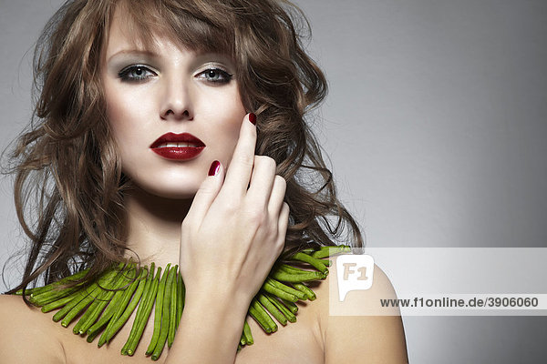 Portrait einer jungen Frau mit grünen Bohnen als Halskette streicht sich mit der Hand über die Wange  Schmuck