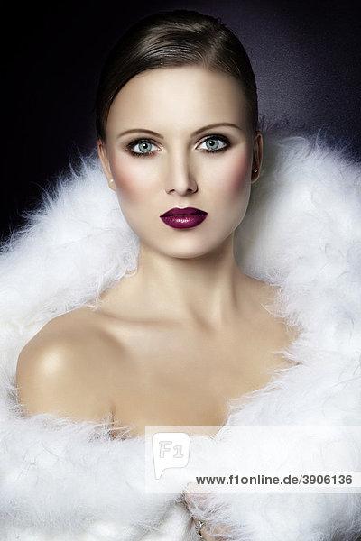 Portrait einer jungen Frau,  eingehüllt in ein weißes Fell,  tiefroter Lippenstift,  direkter Blick,  Fashion,  Glamour