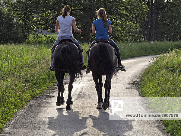 2 junge Reiterinnen auf Fahrweg