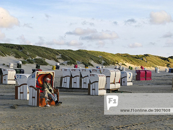 Elderly people sitting in a roofed wicker beach chair as windshelter on the beach at Norddorf  island of Amrum  Schleswig-Holstein  Germany  Europe