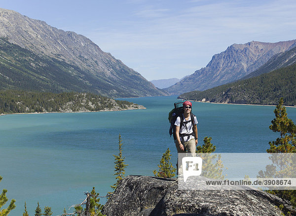 Young woman hiking  backpacking  hiker with backpack  historic Chilkoot Pass  Chilkoot Trail  Lake Bennett behind  Yukon Territory  British Columbia  B. C.  Canada