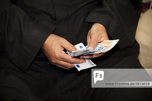 Arabian man holding euro banknotes in his hands