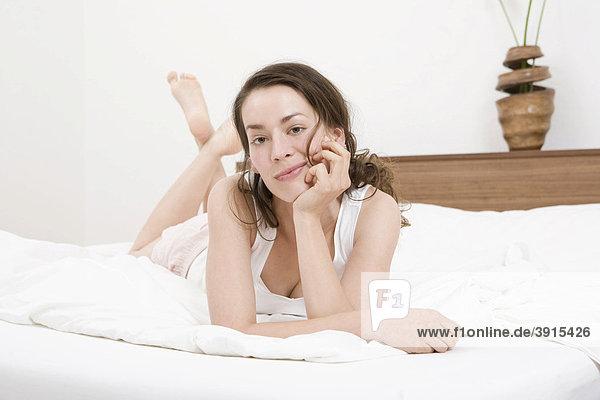 Junge Frau auf Bett
