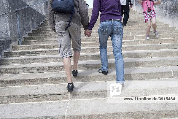 Junges Paar geht gemeinsam die Treppe hoch  Hand in Hand  von hinten