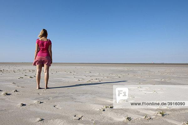 Junge Frau  20-25 Jahre  steht am weiten Sandstrand von St Peter Ording und blickt in die Ferne  Nordsee  Nordfriesland  Schleswig-Holstein  Norddeutschland  Deutschland  Europa