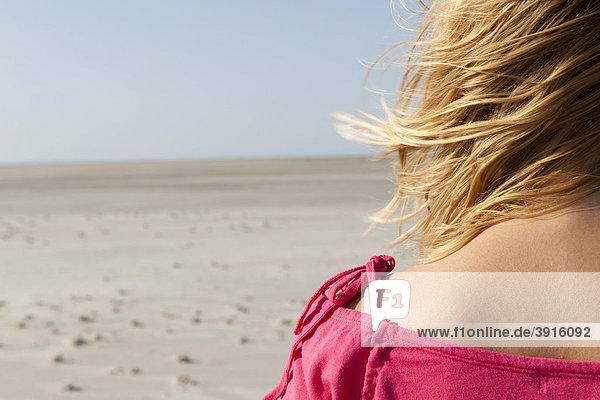 Junge Frau  20-25 Jahre  an einem windigen Tag am Strand von St Peter Ording  Nordsee  Nordfriesland  Schleswig-Holstein  Norddeutschland  Deutschland  Europa