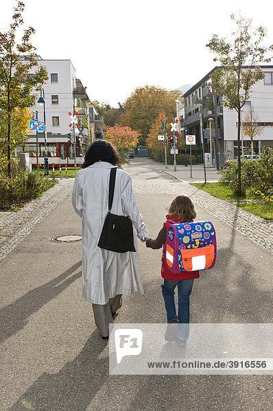 Frau bringt Kind zur Schule