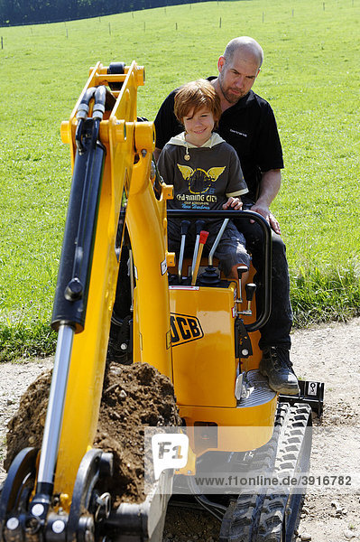Kind mit seinem Vater auf einem Minibagger  Bagger fahren