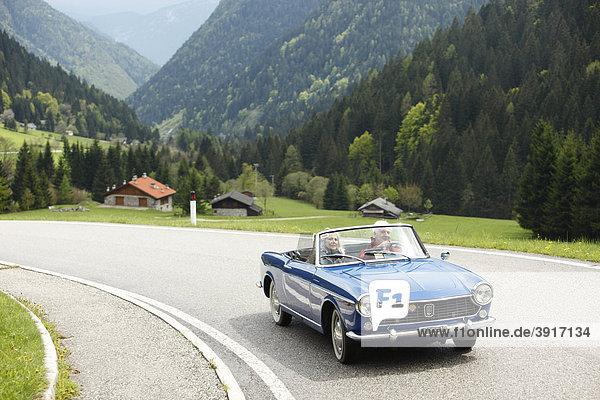 Seniorenpaar fährt im Cabrio  Norditalien  Europa  Telve  Dolomiten