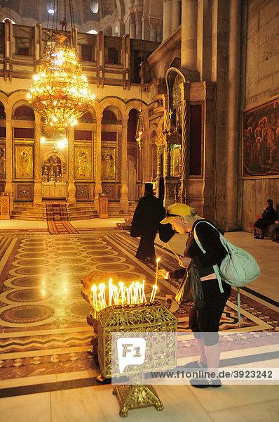 Christliche Pilgerin zündet Kerze an  Grabeskirche  Jerusalem  Israel  Naher Osten  Orient