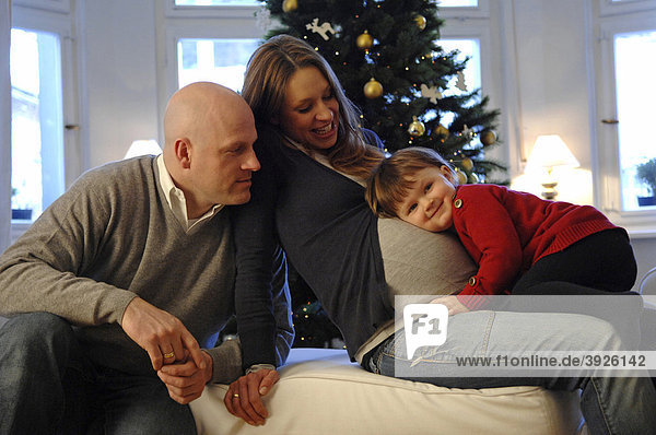 Glückliche Familie mit Tochter,  Vater und schwangerer Mutter,  Weihnachtsbaum