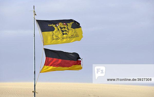 Flaggen von Deutschland und Baden-Württemberg wehen im Wüstensand Flaggen von Deutschland und Baden-Württemberg wehen im Wüstensand