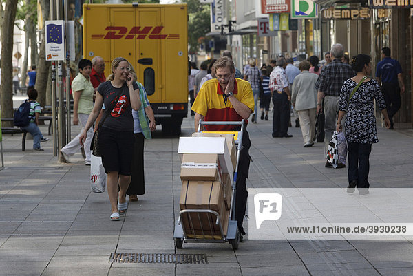 Parcel carrier Michael Meindel balancing a stack of packages across the street with his cart for the Deutsche Post German mail in downtown Stuttgart  Baden-Wuerttemberg  Germany  Europe