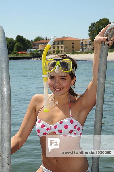 Badende Frau mit Schnorchel kommt aus dem Meer