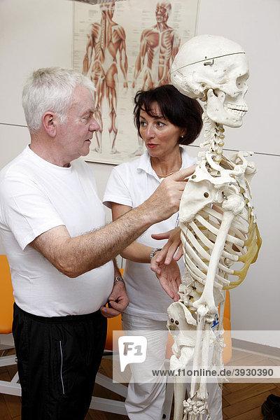 Therapeutin erklärt einem Patienten die anatomischen Grundlagen für eine physiotherapeutische Behandlung anhand eines Skelettes  Krankengymnastik Abteilung in einem Krankenhaus  stationäre und ambulante Behandlung von Patienten  Gelsenkirchen  Nordrhein-Westfalen  Deutschland  Europa