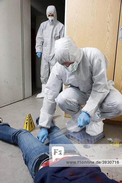 Faserspuren und Mikrospuren werden mit großem Klebeband gesichert  Beamte der KTU  Abteilung Kriminaltechnische Untersuchung der Kriminalpolizei  bei der Spurensicherung an einem Tatort  nach einem Kapitalverbrechen  Tötungsdelikt  gestellte Szene