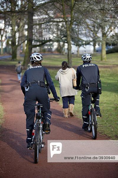 Fahrradstreife der Polizei in einem Stadtpark  Deutschland  Europa