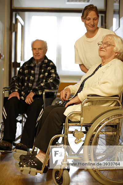 Zwei alte Leute im Rollstuhl mit der Pflegerin