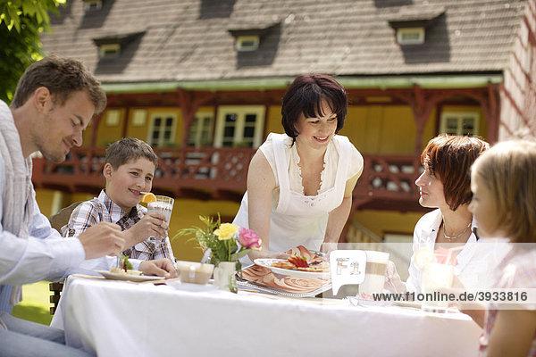 Gartenrestaurant mit Familie und Bedienung